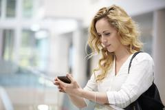 Blonde haired young woman uses smartphone in modern interior Stock Photos