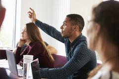 Students Asking Question Whilst Attending Lecture On Campus Stock Photos