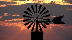 Traditional rustic old windmill spinning silhouette and sunset red clouds sky Stock Footage