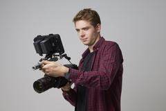 Studio Portrait Of Male Videographer With Film Camera Stock Photos