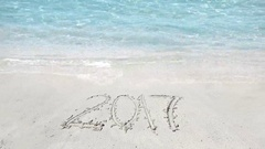 2017 written on beach sand, clear turquoise sea water, tropical exotic holiday Stock Footage