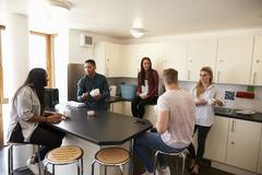 Students Relaxing In Kitchen Of Shared Accommodation Stock Photos
