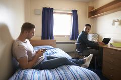 Male Students Working In Bedroom Of Campus Accommodation Stock Photos