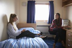 Female Students Working In Bedroom Of Campus Accommodation Stock Photos