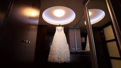 White wedding dress hanging in the dark room Stock Footage