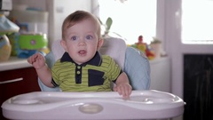 Cute smiling baby eating, sitting at baby seat at home. Mother Feeding her Stock Footage
