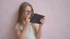 Little girl of 7 years old using ipad tablet pc at home Stock Footage