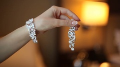 Woman with diamond bracelet holding earrings Stock Footage
