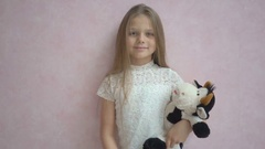 Cute little girl in casual clothes holding a soft toy and smiling at camera Stock Footage