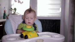 Baby boy playing with a toy car, sitting in a baby chair. One year old baby Stock Footage