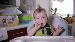 Curious funny baby looking around, sitting in baby chair Stock Footage