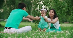 Young Asian family with a year-old girl in the Park teach your child to do first Stock Footage