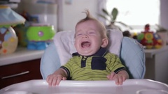 Small naughty child does not want to eat. Crying baby at home kitchen Stock Footage