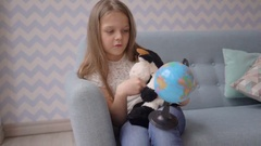 Cute girl holding and rotate a small globe while sitting on sofa at home Stock Footage