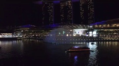 Aerial of water and light show at night in Singapore City Stock Footage