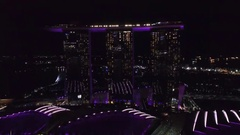 Aerial of three illuminated skyscrapers at night in Singapore City Stock Footage