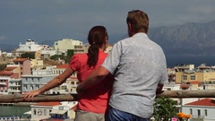 Tourists, young couple, on a hillside and look down on the colorful city. Stock Footage