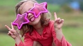 Funny girl in big glasses in shape of stars looks at camera and makes grimaces HD Footage
