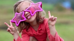 Funny girl in big glasses in shape of stars looks at camera and makes grimaces Stock Footage