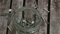 Nails falling into a jar Stock Footage