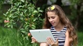 Pretty girl in sunglasses with tablet pc stands under apple tree in garden HD Footage