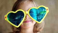 Funny little girl in yellow and blue glasses looks at camera and shows tongue Stock Footage
