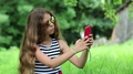 Beautiful girl with long hair makes selfie on his smartphone HD Footage