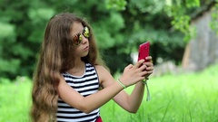 Beautiful girl with long hair makes selfie on his smartphone Stock Footage