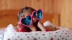 Funny girl in big glasses in the shape of hearts lies on the bed Stock Footage