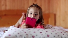 Little girl with smartphone lies on the bed Stock Footage