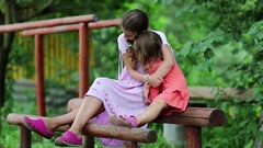 Two sisters sits on a wooden log at a sports ground and embraces Stock Footage