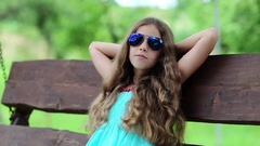 Girl with blue sunglasses rests on the bench in park Stock Footage