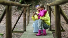 Mother and little daughter with smartphone on foot bridge Stock Footage