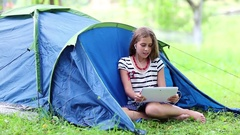 Pretty girl sits on grass near tourist tent and communicates via tablet computer Stock Footage