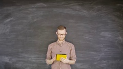 4K Portrait smiling man with tablet computer on blank chalkboard background Stock Footage
