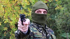 Man in military uniform and green mask with black revolver in hand Stock Footage