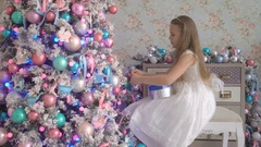 Cute little girl in white dress decorating Christmas tree at home Stock Footage