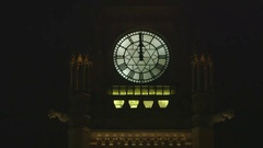 Shot of a clock tower with moving watch hands in the dark. Stock Footage