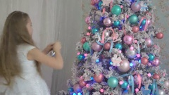 Cute little girl in white dress decorating a Christmas tree at home Stock Footage