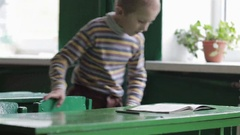 Boy sit on a school desk Stock Footage