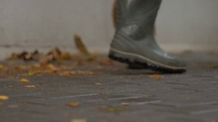 Janitor in rubber boots sweeps leaves Stock Footage