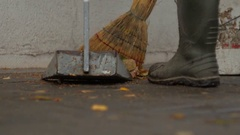 Janitor in rubber boots sweeping leaves Stock Footage