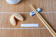 Fortune Cookie With Blank Slip and Chopsticks and Cups Stock Photos