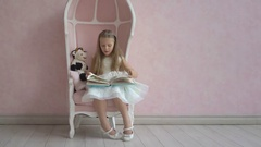 Elegant little girl with long hair in white dress sit on pink chair and reading Stock Footage