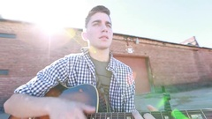 Teenager Plays Guitar with Old Brick Buildings Stock Footage