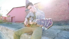 Teenager Plays Guitar in Slow Motion with Old Brick Buildings Stock Footage