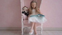 Lovely little girl with long hair in white dress sit on pink chair and reading Stock Footage