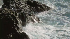 Amazing Atlantic waves are breaking of black basalt cliffs in sunny day on Stock Footage