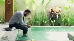 Sad, unhappy businessman sitting by pool in outdoor villa Stock Footage