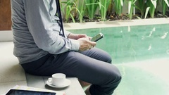 Businessman using smartphone sitting by pool in outdoor villa  Stock Footage